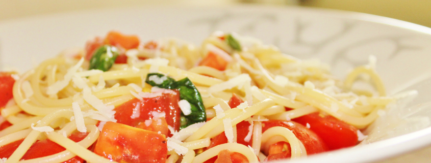 a bowl of spaghetti with tomatoes and basil on top
